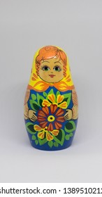 Russian doll standing in an off white background