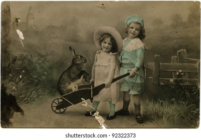 RUSSIAN EMPIRE - CIRCA 1901: Reproduction of antique greeting Easter  postcard shows Two girls with a rabbit in a wheelbarrow, circa 1901