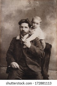 RUSSIAN EMPIRE, LUGANSK, now UKRAINE - CIRCA 1910s: An antique photo shows studio portrait of a bearded man in formal suit sitting in a chair, a small boy stands behind him and hugs his father