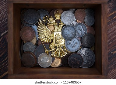 The Russian Empire's old coins in the background of the coat of arms