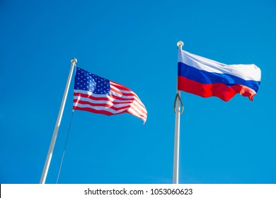 Russian Federation and USA United States of America flags on a blue sky background. idea of the sanctions war combat negotiation and confrontation