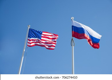 Russian Federation and USA United States of America flags on a blue sky background. idea of the sanctions war combat negotiation and confrontation. US and Russia flag