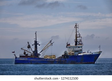 A Russian fish trawler on anchor in calm water with the fishing nets stowed on deck