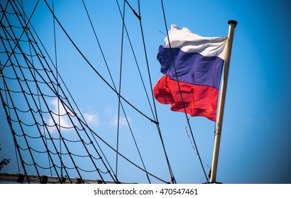 Russian flag near shipboard ropes