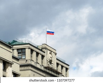 Russian flag on the Parliament building in Moscow against cloudy sky. State Duma, authority of Russia
