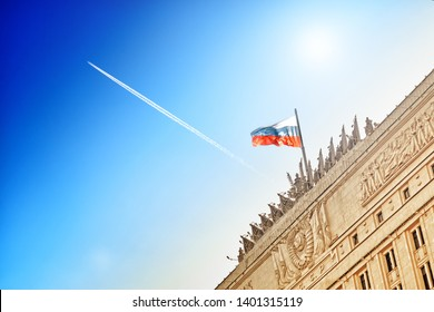 russian flag waving on top of ministry of defense building in moscow city russia against blue sky with airplane flying high aerial view of aircraft contrail and old stalin era architecture landscape