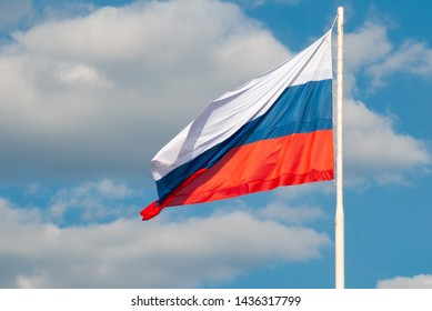 Russian flag waving in the wind against the blue sky - Shutterstock ID 1436317799