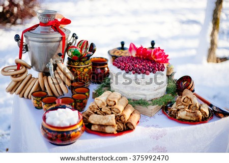 Russian folk decor table with a samovar, pancakes and bagels