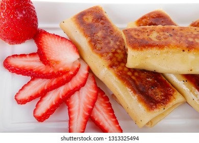 russian food - cottage cheese wrapped in sweet a pancake with strawberry served on white plate isolated over white