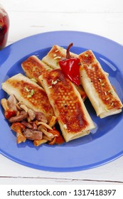 russian food - meat wrapped in a pancake with red hot pepper  and pickled mushrooms served on blue plate over wooden table in restaurant