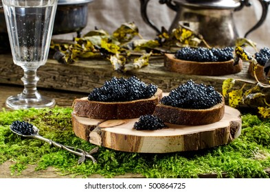 Russian food. Sandwiches with black caviar. Black bread. Vodka. vintage shot glass. silverware. The old Board and moss. Autumn withered leaves.