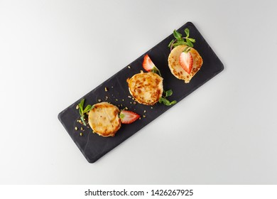 Russian fried quark pancakes made of fresh cottage cheese with strawberries, nuts and mint leaves, as a part of sweet breakfast, isolated on white