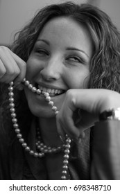 Russian girl with curly hair playing with beads around her neck