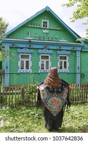 A russian girl dressed in the shawl from Pavlovsky Posad against the background of the wooden house