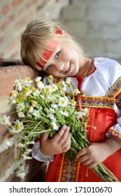 Russian girl in national costume with flowers