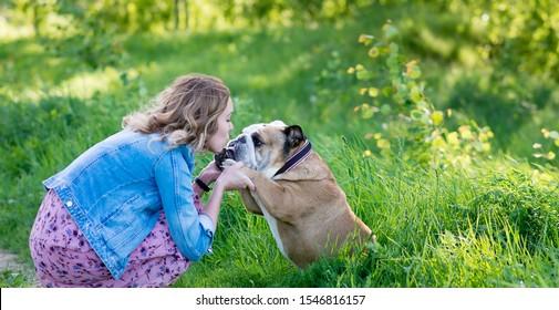 Russisches Mädchen, das mit englischem Bulldog im Park spielt, Garten