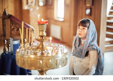 Russian girl praying in front of icons in the Orthodox Church