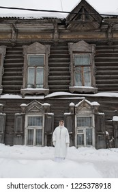 Russian girl and wooden house in Tomsk city (Russia)