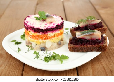 Russian herring salad  and sandwiches on plate on wooden table background
