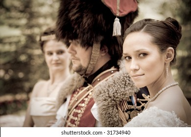 Russian hussar in vintage outfit with two pretty women.