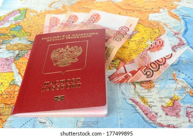 Russian international passport with money within and origami plane made from money on the world map