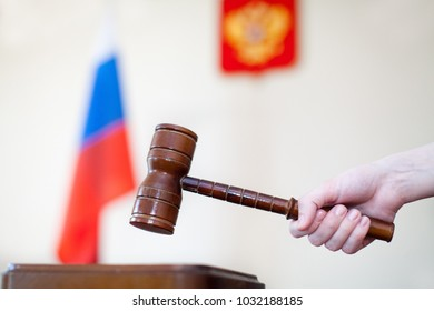 Russian justice. Wooden gavel in female hand and russian flag on a background.