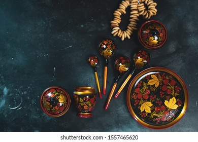 Russian khokhloma set, traditional wood painting handicraft souvenirs top view black background