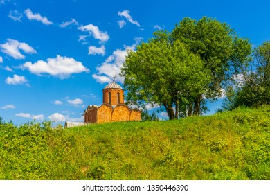 Russian landscape with green trees, grass and ancient orthodox temple against blue sky. Beautiful scenery and architectural landmark. Church of the Savior on Kovalev, Velikiy Novgorod vicinity, Russia