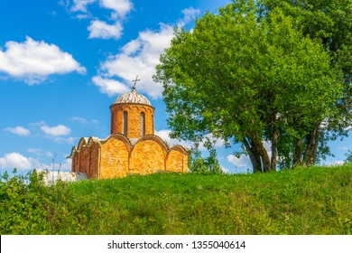 Russian landscape, green trees, grass and ancient orthodox temple against blue sky. Beautiful scenery and architectural landmark. Church of Our Saviour on Kovalev, Velikiy Novgorod vicinity, Russia