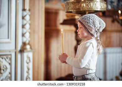 Russian little girl in a scarf on her head stands in an Orthodox Church, lights a candle and prays in front of the icon.