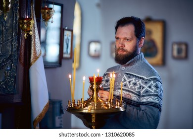 A Russian man with a beard stands in an Orthodox Church, lights a candle and prays in front of the icon.