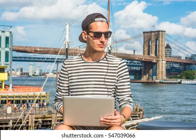 Russian man travels, works in New York, wearing striped long sleeve T shirt, cap worn backward, sunglasses, sits by river, works on laptop computer, listens music with earphone. Color filtered effect.