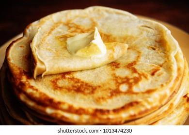 Russian Maslenitsa, Shrovetide, pancake week, carnival, shrove, pancake day. a stack of pancakes with butter upstairs on plate, on wooden background, close-up