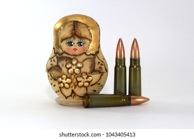 Russian matryoshka and several cartridges for a Kalashnikov assault rifle on a white background close-up