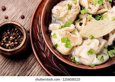 Russian meat dumplings pelmeni on wooden rustic background.Russian pelmeni