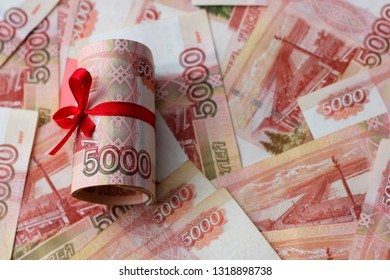 Russian money 5000 rubles twisted into a tube and tied with a ribbon, against the background of bills, the color of the year according to the version of Panton