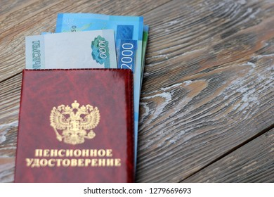 Russian money and a pension certificate. Russian translation: Pension Fund of the Russian Federation. Pensioner's ID on the wooden background, concept of pension reform, selective focus