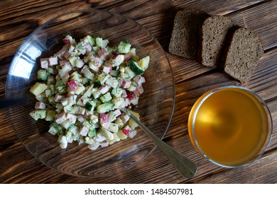 Russian national dish - okroshka. Cold soup with meat, vegetables and kvass. Separate cooking. Black bread. Wooden surface from pine boards. Daylight
