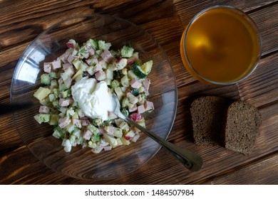 Russian national dish - okroshka with sour cream. Cold soup with meat, vegetables and kvass. Separate cooking. Two slices of black bread. Wooden surface from pine boards. Daylight