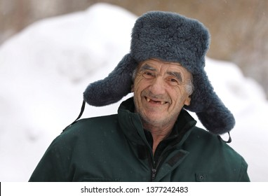 Russian old man in winter hat smiles and shows his mouth without teeth. This pensioner must to see a dentist as soon as possible