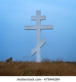Russian orthodox christian cross in the field at twilight