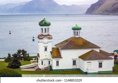 The Russian Orthodox Church in Dutch Harbor Alaska. Built in 1894, it is one of the oldest churches in Alaska. The red and green buoys in the background are an aide to navigation.