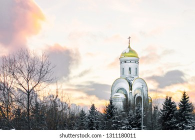 Russian Orthodox Church with the sunset sky on the background, first at the bottom. White wall of the church, golden dome and orange sky. Greek orthodox, Moscow Church