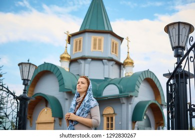 Russian Orthodox middle-aged woman in a scarf stands on the background of the Orthodox wooden Church.