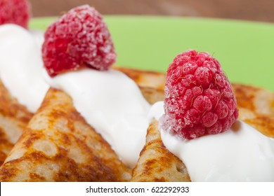 Russian pancakes - blini with sour cream topping. Selective focus.