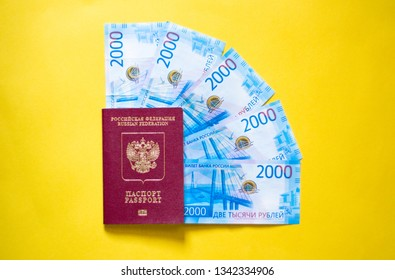 russian passport and new russian money 2000 rubles on yellow background