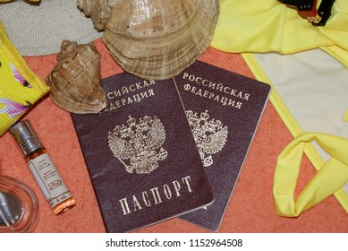 Russian passport on an orange background, a swimsuit, a hat, glasses, perfume, seashells.