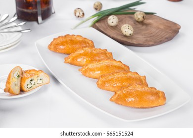 Russian pastry pirozhki on white background in restaurant table.