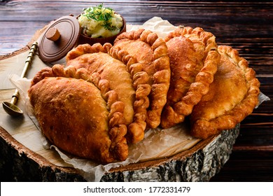 Russian Patties Pasties, Hot Cakes, Pirozhki, Pies on wooden cupboard . Traditional homemade fried pies with potatoes