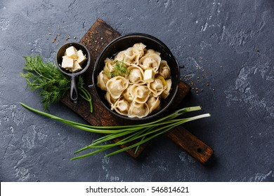 Russian pelmeni meat Dumplings with butter and greens in black iron pot on dark stone background